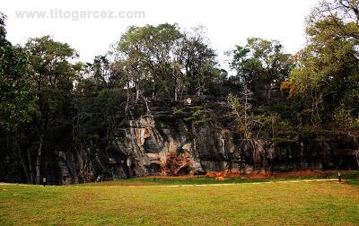 Paredão rochoso em meio a muito verde na gruta da Lapinha, em Minas Gerais