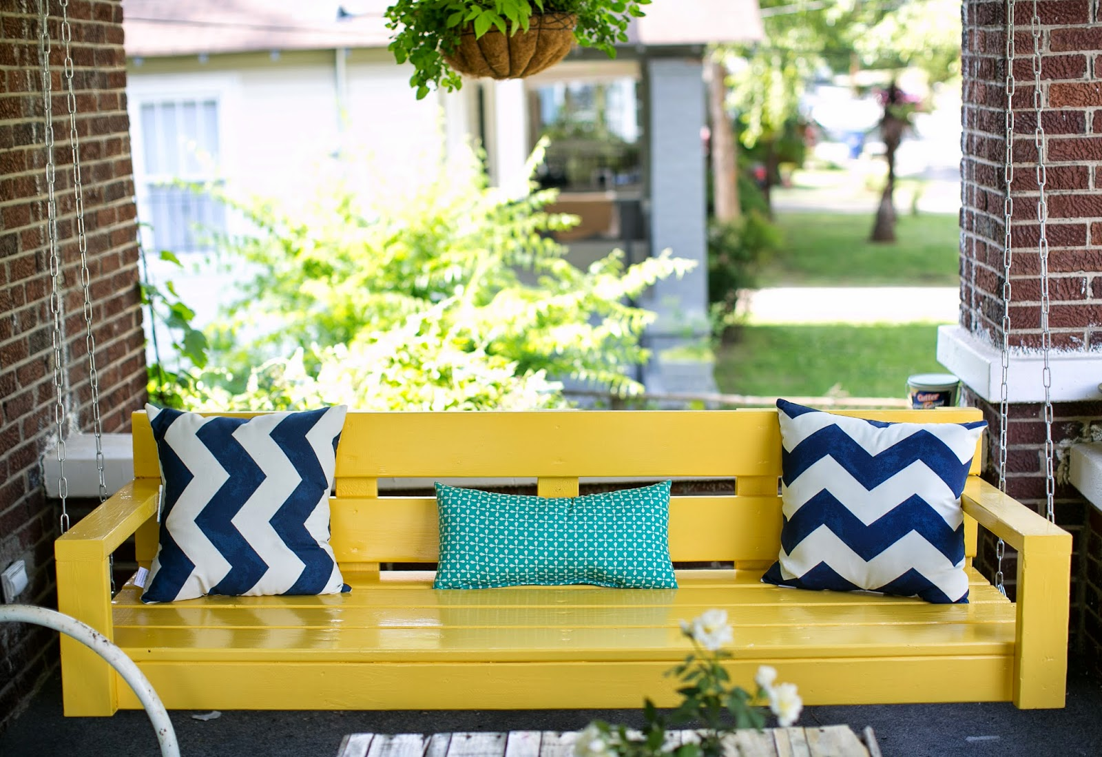 yellow DIY porch swing with chevron cushions from Target