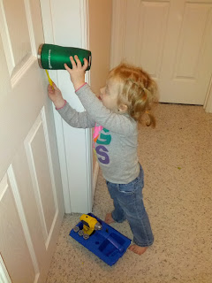 Lily holding a cup over the doorknob and using a plastic screwdriver
