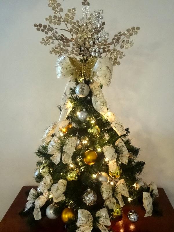 decoracao de arvore de natal azul e prata: de fita ramos dourados uma borboleta dourada para finalizar o laço e