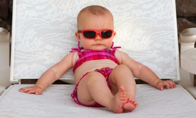 Foto bayi lucu memakai kacamata hitam dan merah lagi santai
