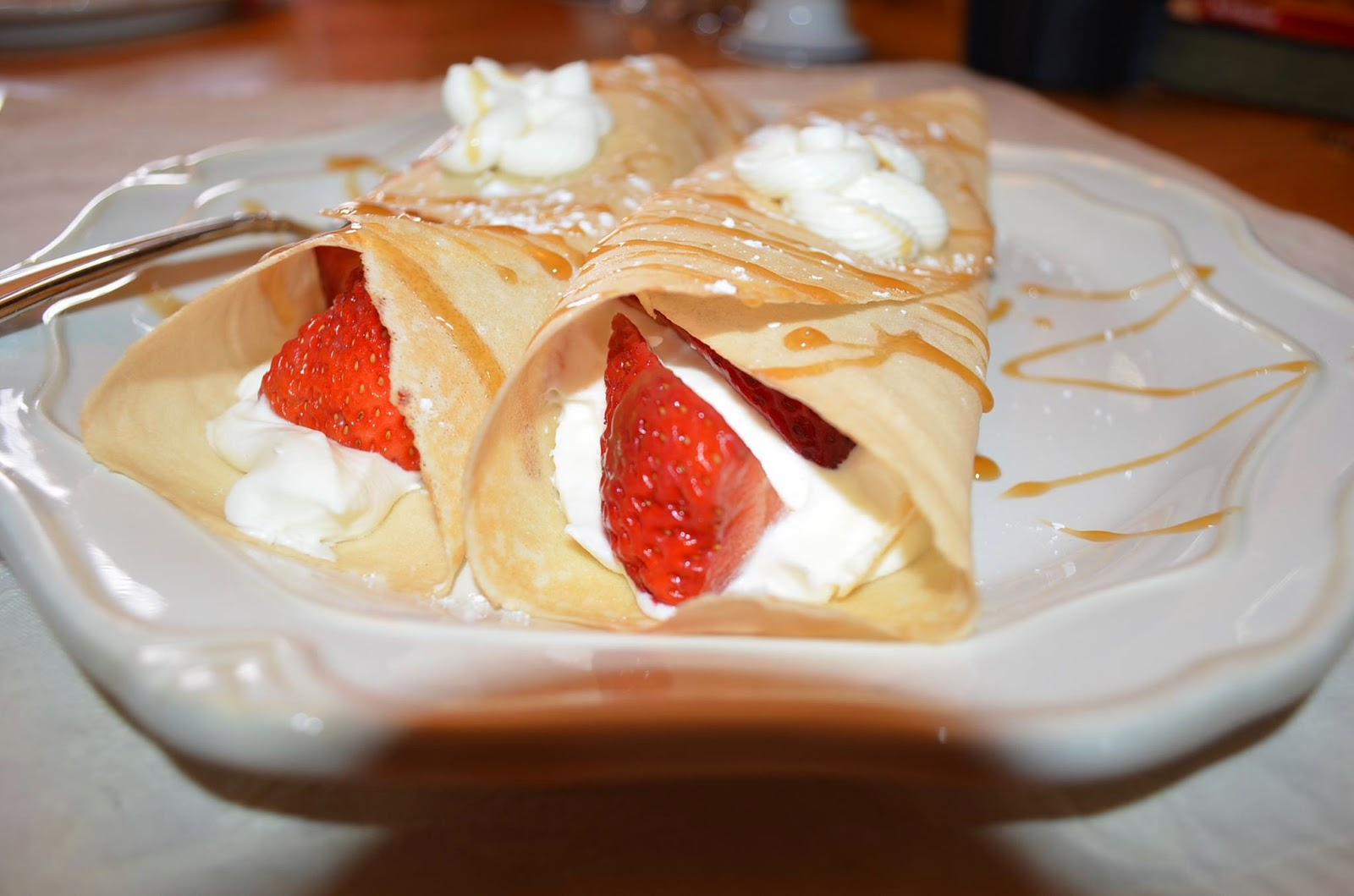 Strawberry Crepes on the plate with caramel sauce