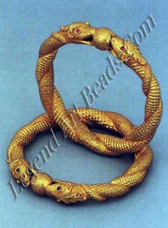Two intertwined gold serpents, their bodies worked with distinctive scale patterns, hold aloft a celestial jewel. The snake is a potent symbol in Hinduism. Sexual energy (kundalini), the serpent power, is believed to lie coiled at the base of the spine.