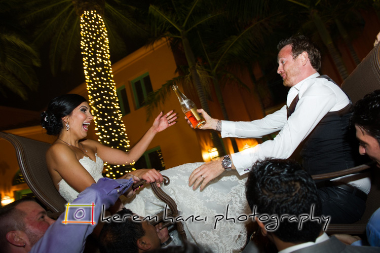 The newly weds are enjoying a bottle of champagne during their Hora Dance