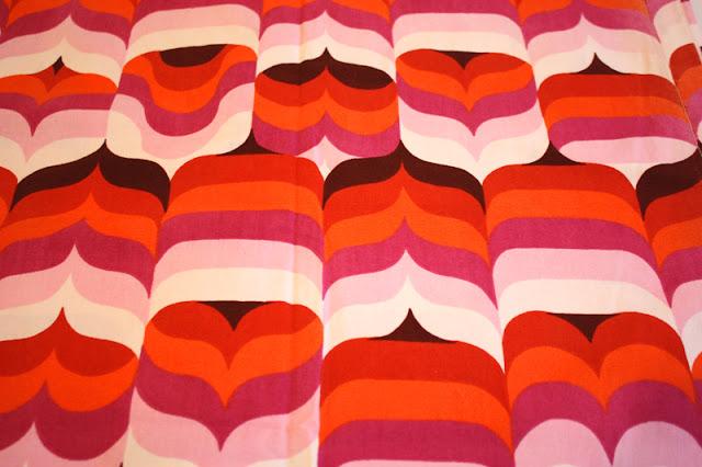 bunter Stoff Farben weiß, braun, rosa, pink, orange rot mit großem Muster und Herzen