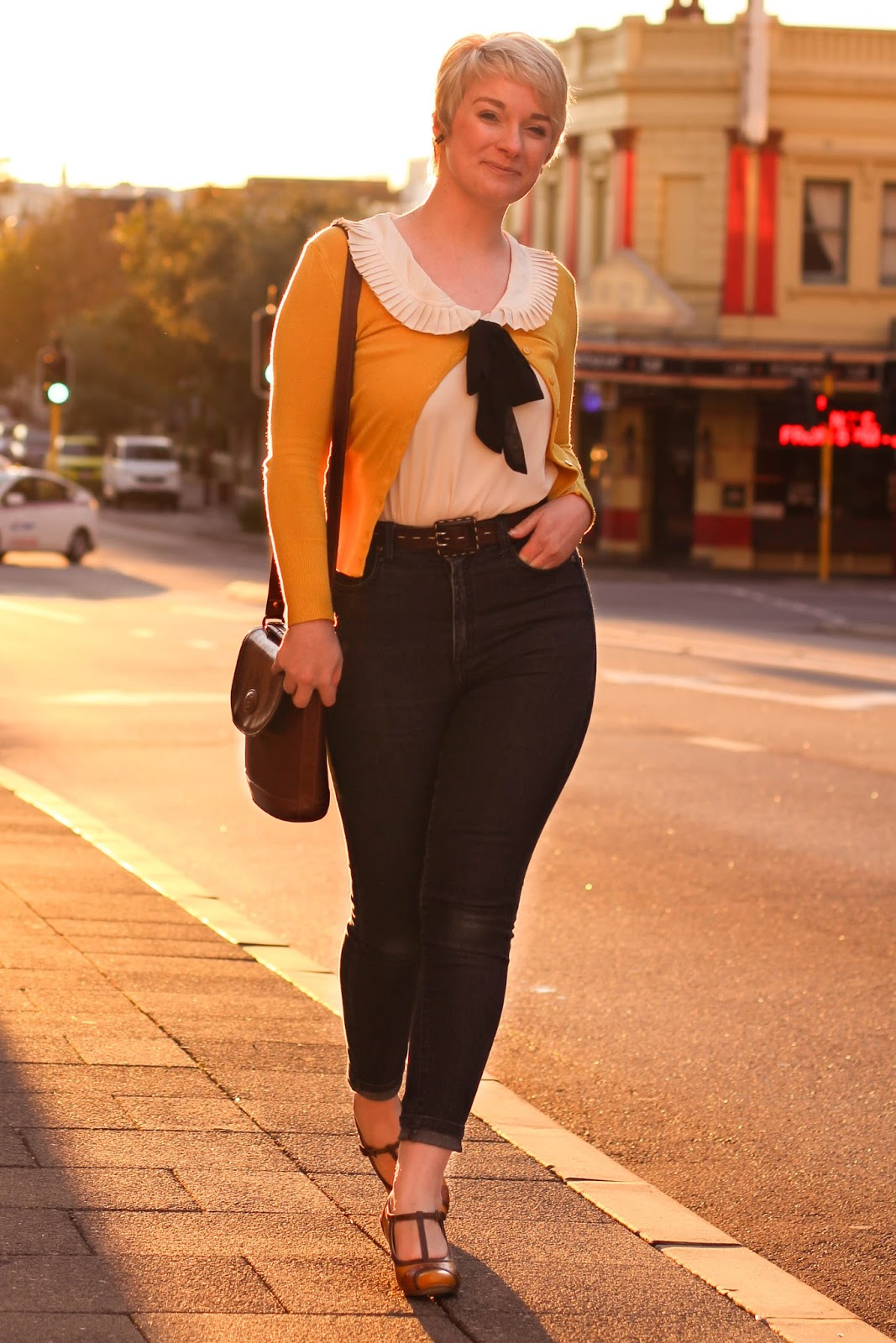 Liana of Finding Femme wears mustard cardigan, pixie cut, peter pan collar Modcloth blouse with black pussy bow neck tie, high rise skinny jeans and Chelsea Crew shoes in Northbridge, Perth.