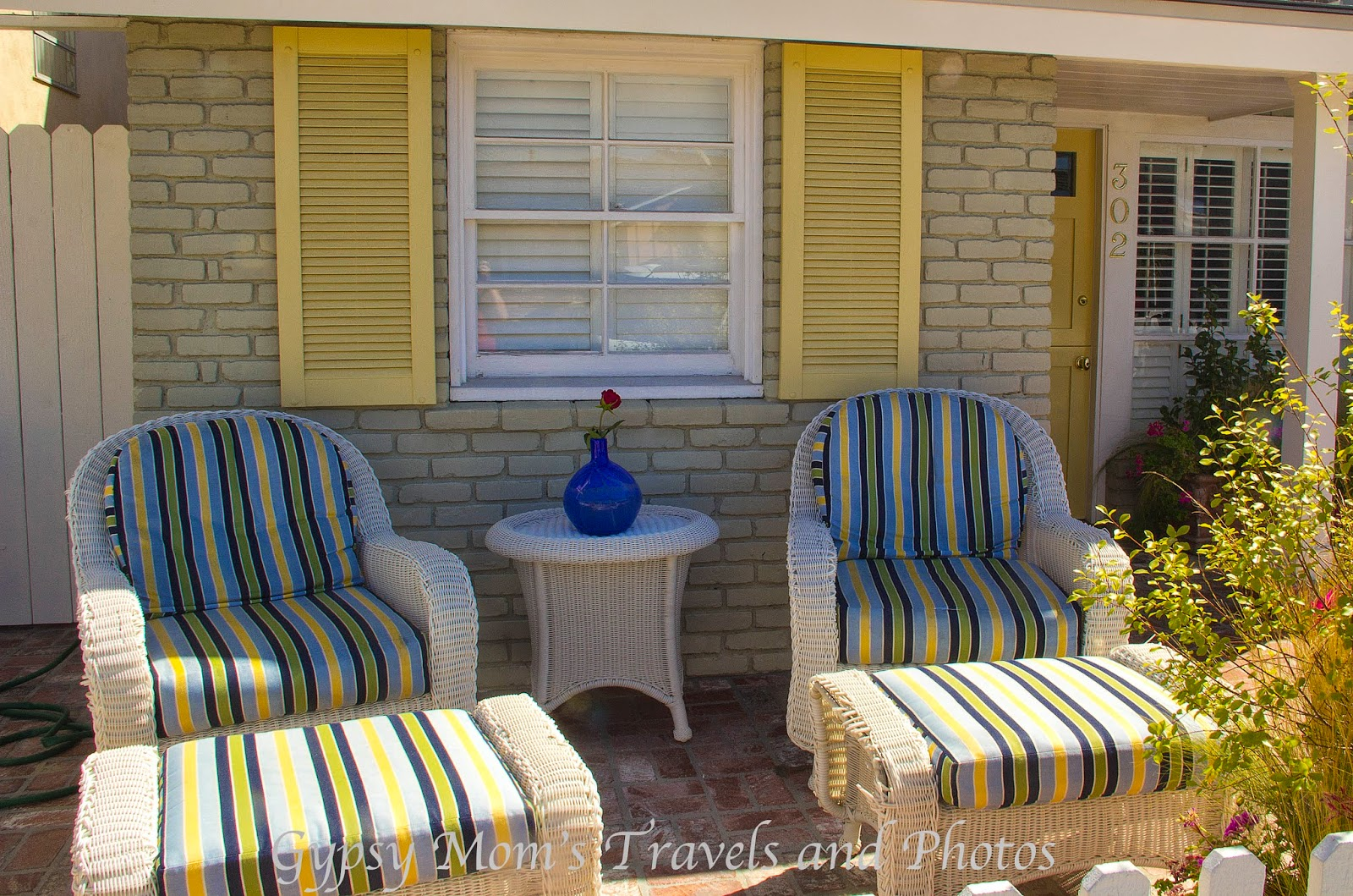 Front patio with yellow shutters on house on Balboa Island