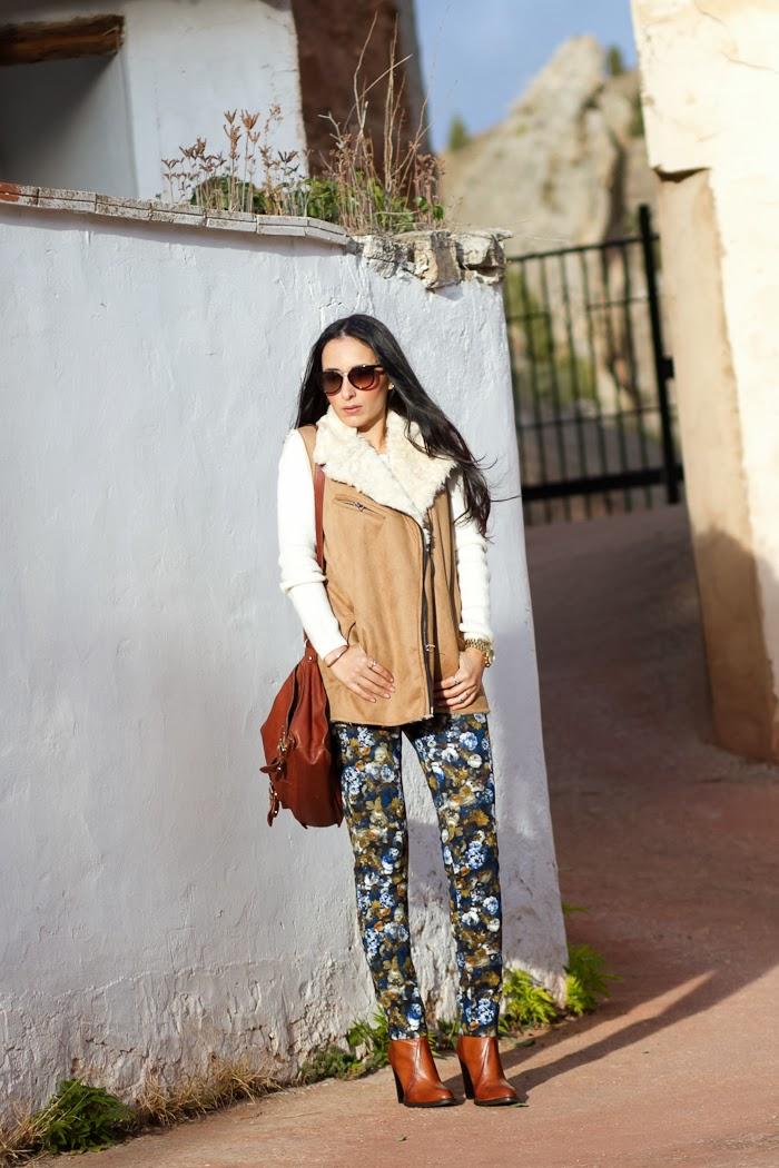 Fashion Blogger con chaleco de pelo, pantalones de flores azules y mostaza de neopreno y botines de Zara