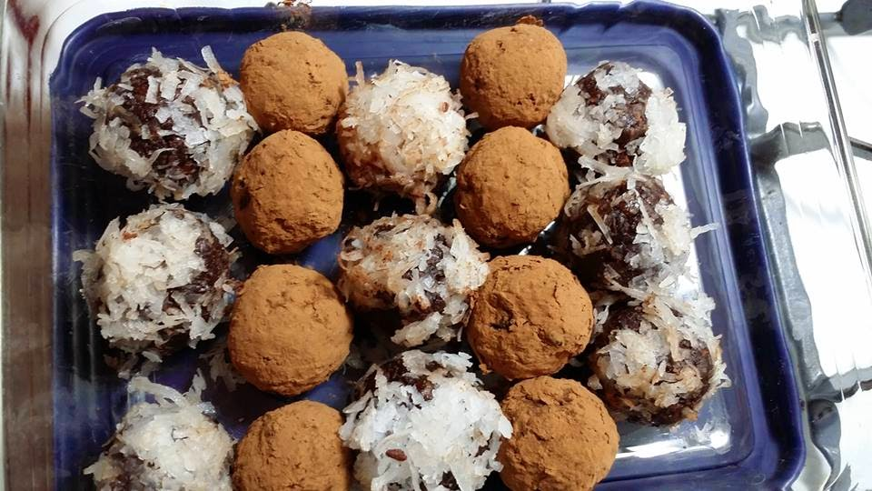A tray of golf ball sized carob cocoa date balls, lined up in rows of alternating coats of flavors: coconut, cocoa powder.