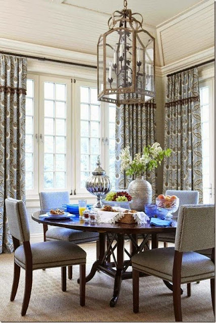 muted blue and beige dining room with upholstered chairs round dining table glass cage light