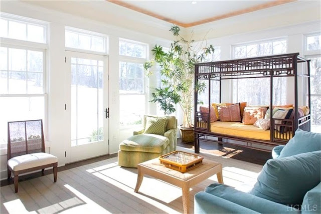 Bright sunroom with wood floor, green armchair and blue sofa in a Bedford, NY home