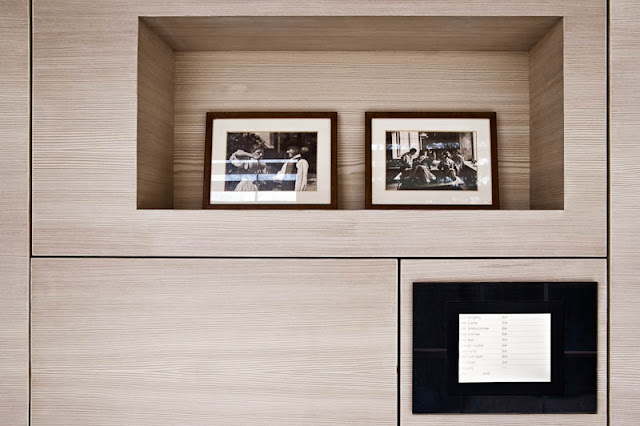 Brown Wooden Wall with Hole which is Filled with Several Black White Photos