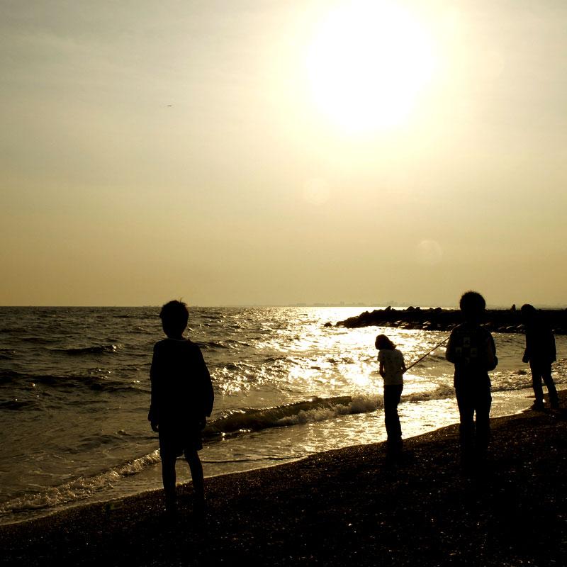 夕方の海で遊ぶ子供