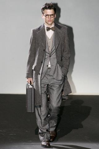 Traje gris, chaleco marrón claro, moño marrón oscuro y abrigo largo de lana. Zapatos con cordón marrón.