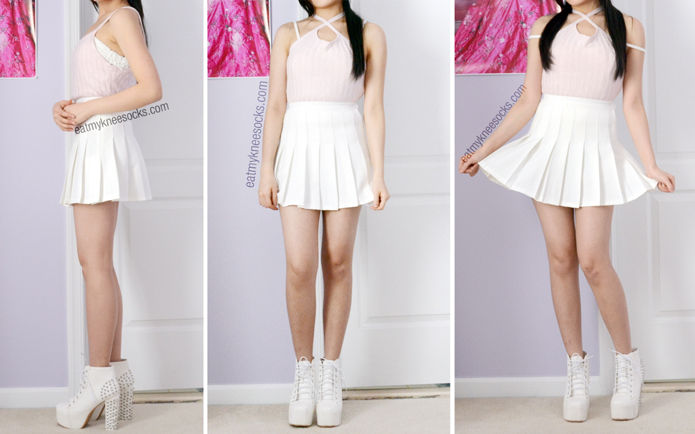 The light pink crop top, modeled with a white pleated tennis skirt and white spiked platform booties.