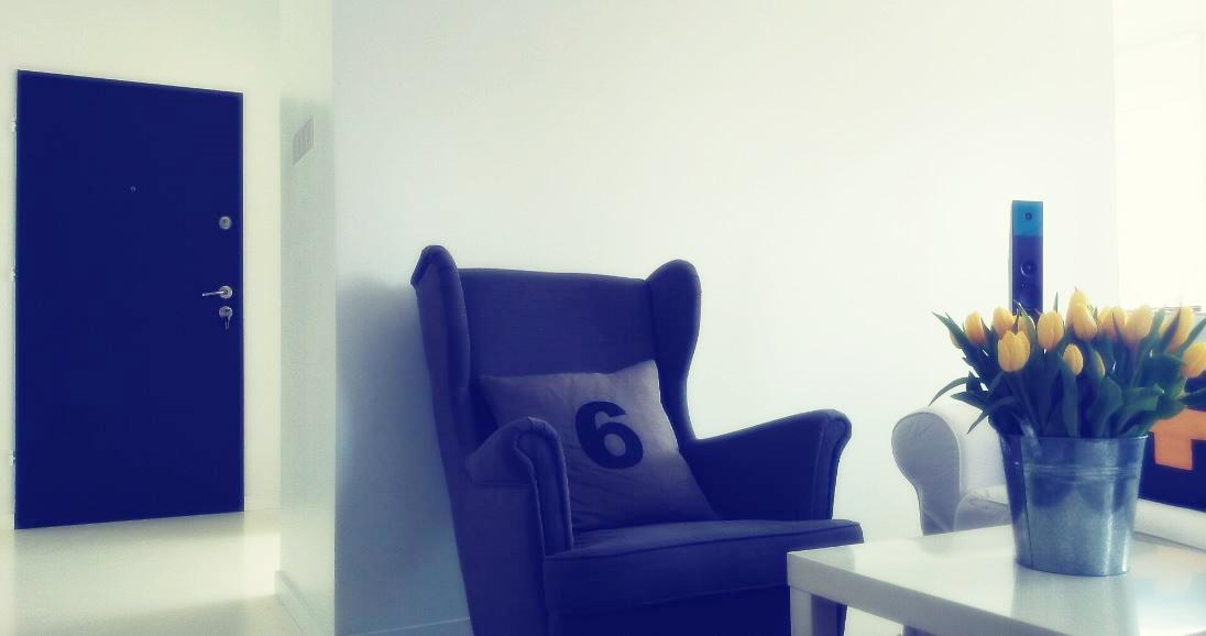 Białe wnętrze, biała podłoga, szary fotel ikea, drzwi malowane farbą tablicową