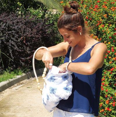 Chica buscando en un bolso de granny square flor africana