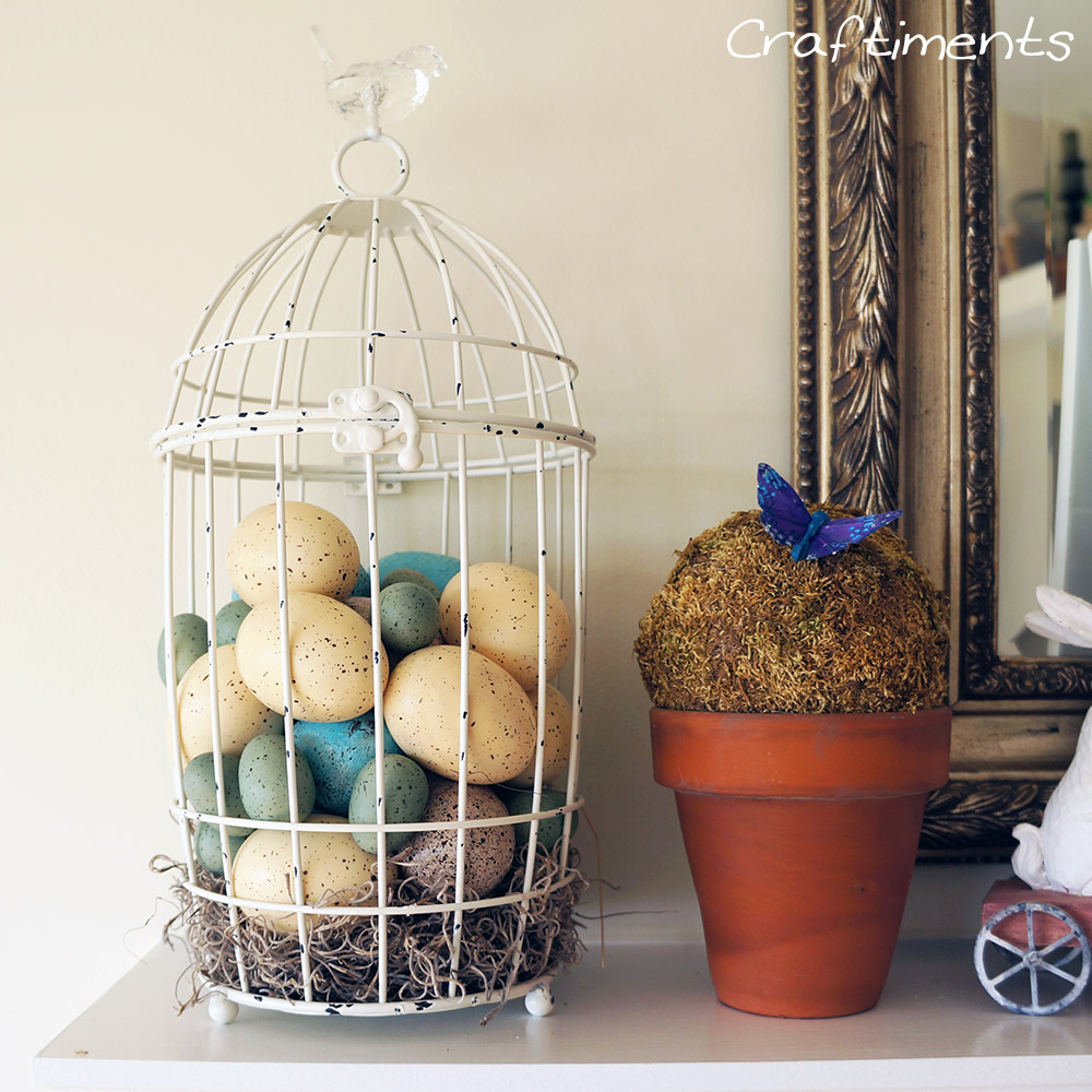 Craftiments:  Bird cage filled with faux eggs and a simple moss topiary in a terracotta flowerpot