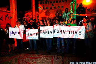 """""""we hate dania furniture"""" sign held together by page 1 partiers"""