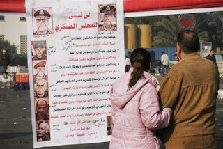 An Egyptian couple looks at an anti-government banner