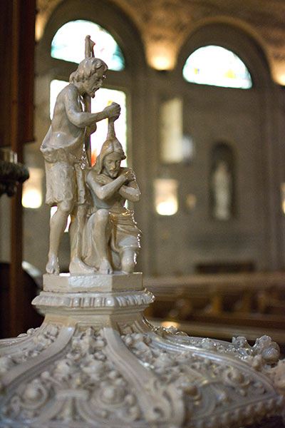 Ornately sculpted white holy water font with sculptures showing a kneeling Jesus being baptized by John the Baptist