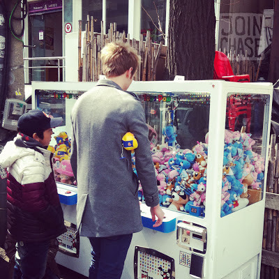 A foreign man and Korean child playing claw machines in Seoul, South Korea.