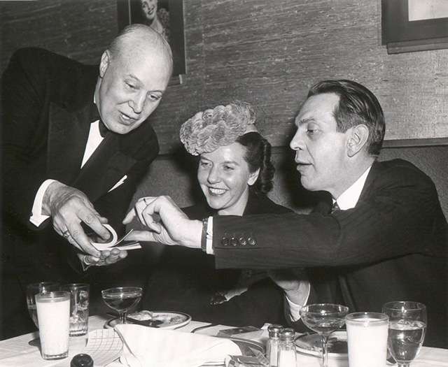 John 'Jack' Spooner entreteniendo a Raymond Massey y señora. Imagen vía LIFE©