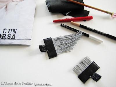 Orecchini asimmetrici ecopelle e frange fra matite da trucco
