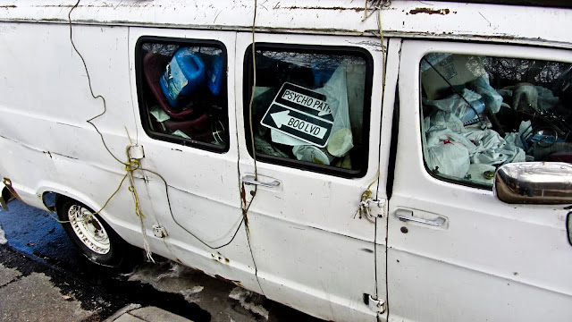 A gross, white, van filled with road signs, garbage, buckets and antifreeze. This strange van scene is either owned by a hoarder or a psychopath or both. Don't get in the van.