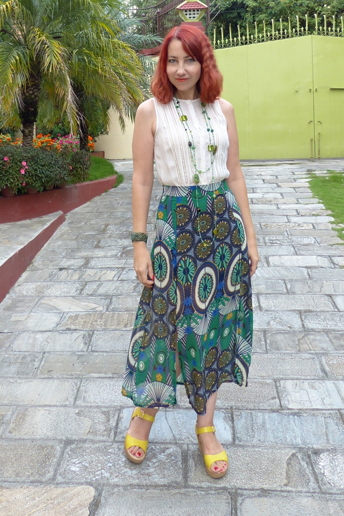 Printed green skirt and beige top accessorized with beaded necklace and bangle