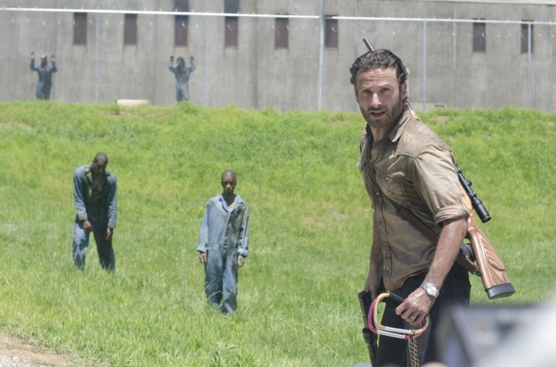 Rick Grimes è nel giardino del carcere, dietro di lui i detenuti zombie si avvicinano