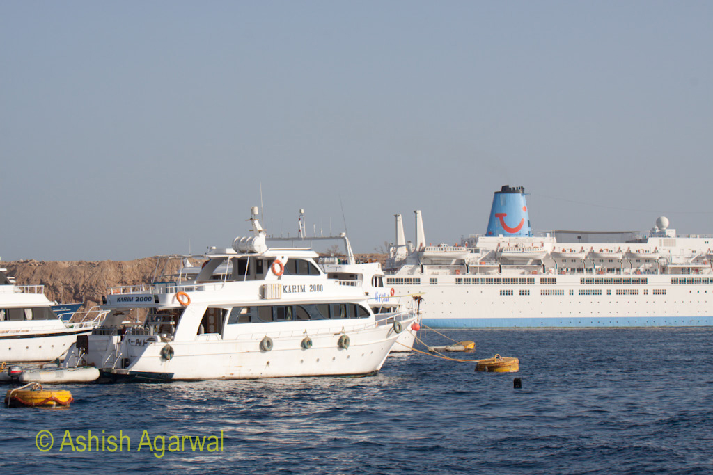 Smaller ships and a large luxury liner in the waters of the Red Sea in Sharm el Sheikh in Egypt