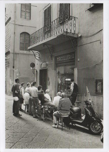 balck and white picture of people watching a television set in a butcher's window