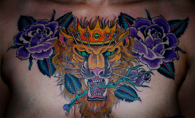 Chest piece tattoo with lions head, purple roses and crown by tattoo artist Jason Kunz for Triumph Tattoo