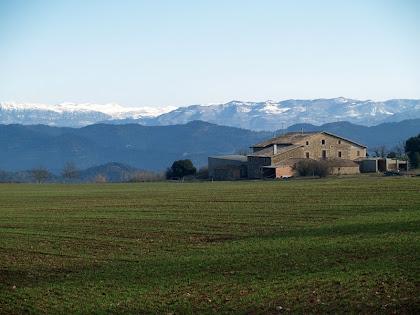 El Vilar envoltada de camps i amb el Pirineu nevat al seu darrere
