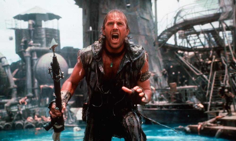 Cena do filme Waterworld - O Segredo das Águas (1995) onde o personagem principal aparece com um arpão na mão gritando