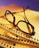 black framed glasses sitting on a pile of notebooks