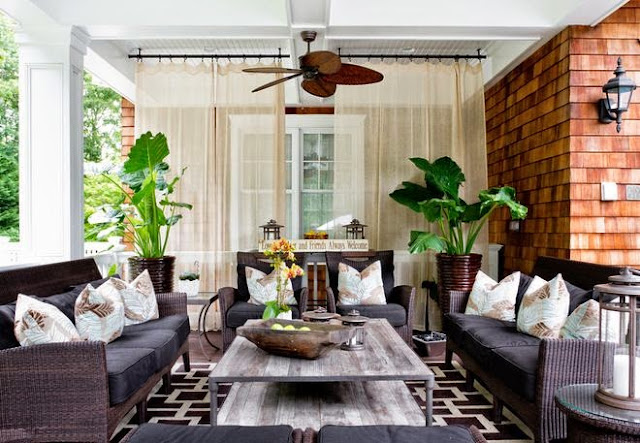 outside open porch lanai with brick fireplace geometric rug ceiling fan