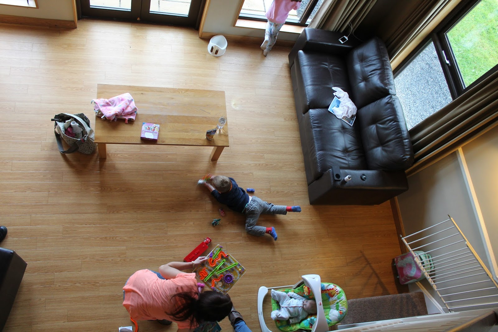 Aerial view of living room with child playing with cars sleeping baby and girl staring out of window