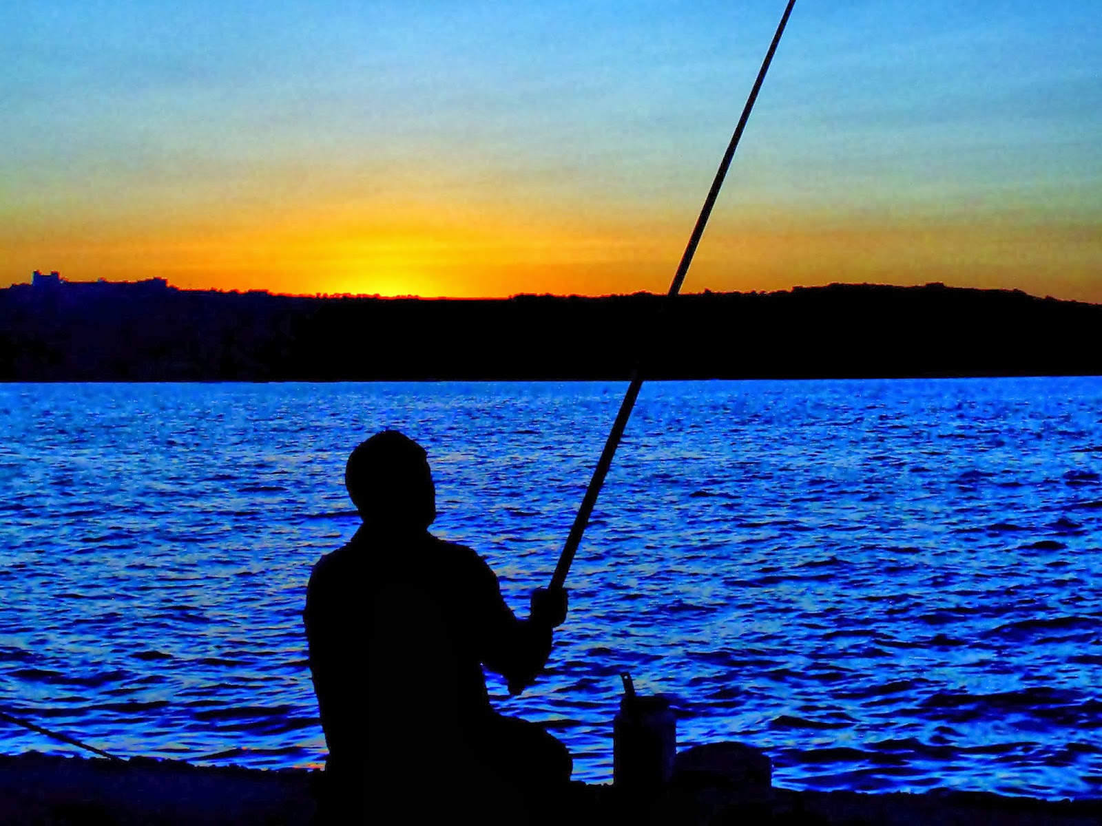 Silhouette of man fishing at sunset.