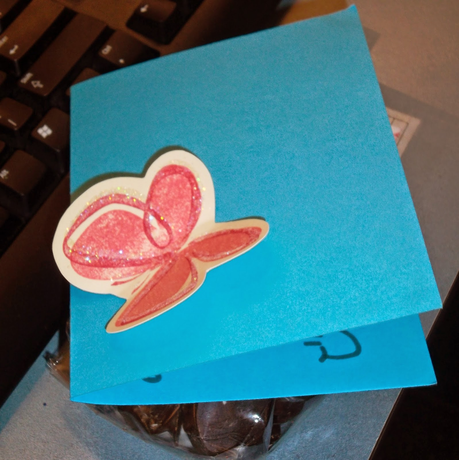 Blue folded card with a pink butterfly pasted on it, sitting on top of a bag of candies