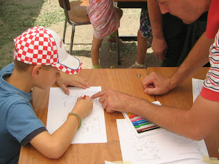 Kisérő áthajol a padon, az óvódás meg figyeli a magyarázatot. A kicsi fején piros-fehér kockás simlisapka, kezében piros ceruza van.