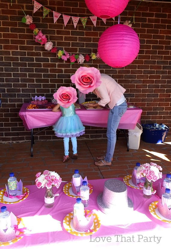 Image of princess birthday party ideas for kids. Cake table, glitter crowns, party supplies and printable paper decorations.