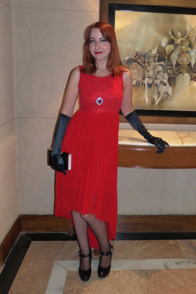 New Year party glamorous outfit: red dress, long black gloves, Swarovski pendant