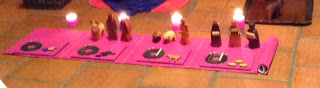 This photo has been cropped, so it is short and long, showing just the Godly Play Advent materials - - a long strip of purple cloth, with four plaques on it (exactly matching the purple of the cloth), various figures from a wooden nativity set, and four lit candles behind it.