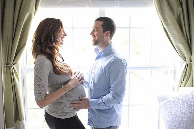 Amy West and husband sharing a moment during 35 week maternity shoot
