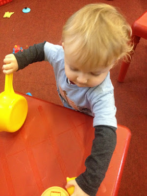 Toddler playing with toy saucepan and concentrating hard