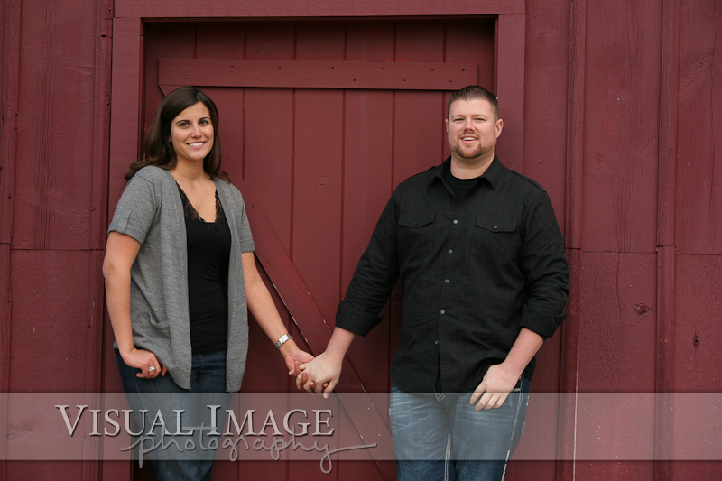 Couple holding hands in front of maroon wood barn door