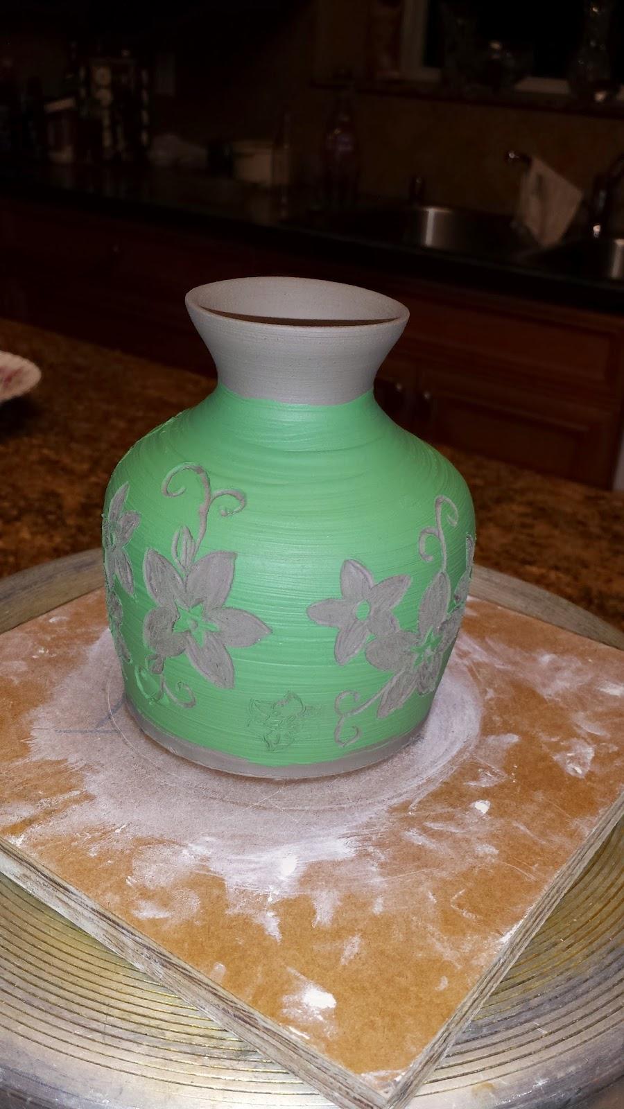 White stoneware vase with sgraffito white flowers on green background, in progress.