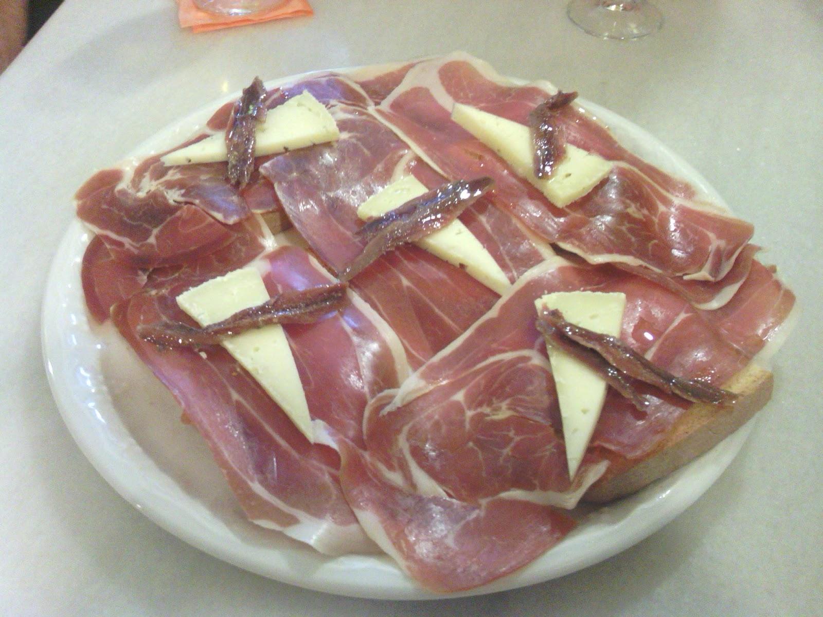 alpargata de jamón y queso. Es una rebanada de pan con aceite, tomate, una buena loncha de jamón serrano, coronada con una cuñita de queso y una anchoa.